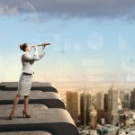 Image of businesswoman looking in telescope standing a top of building